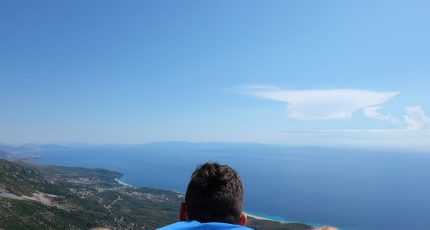 american man logara balcony over ionian sea